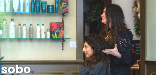 Hair dresser talking to client in chair