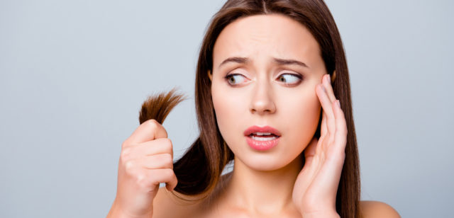 woman looking at the split ends of her hair worryingly